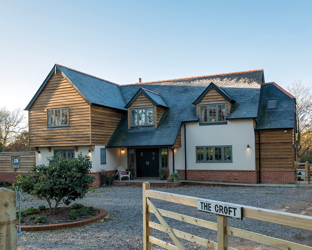 Self build property with timber cladding and green flush casement windows