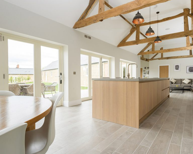 large modern kitchen with oak beams and bi-fold doors