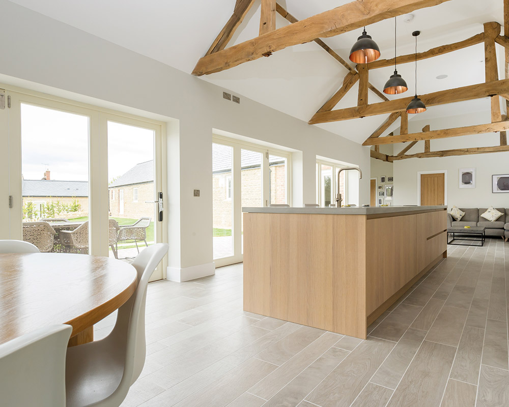 large modern kitchen with oak beams and bi-fold doors