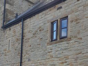 stone building with stained casement windows open